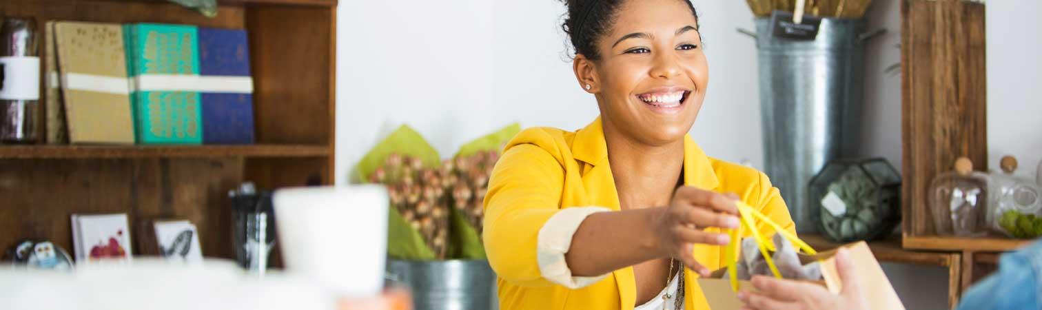 Woman handing bag to customer